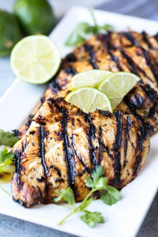 Several margarita grilled chicken breasts on a white serving platter garnished with fresh sliced limes and a sprigs of cilantro