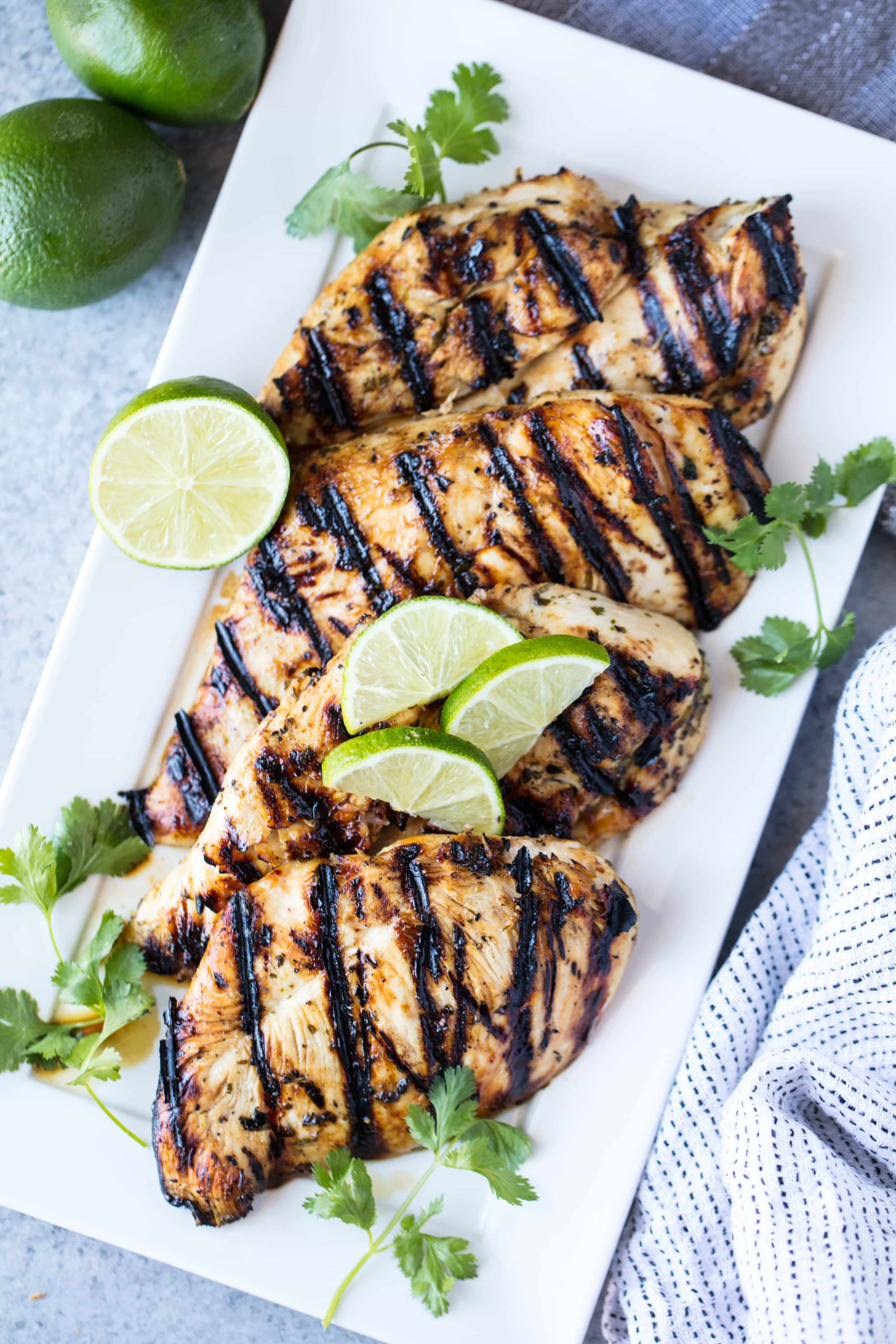 Four pieces of margarita grilled chicken breasts on a white serving platter with some sliced limes on top