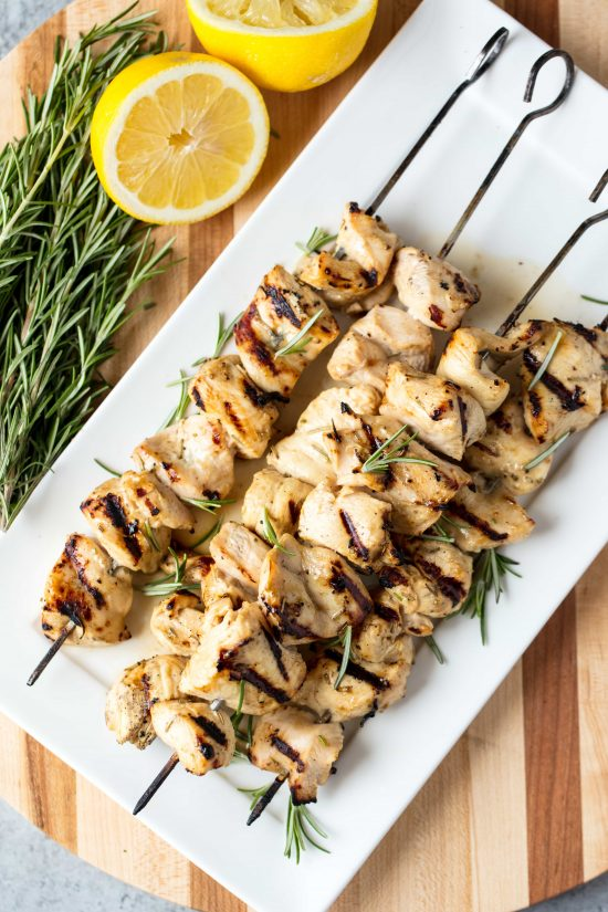Rosemary ranch grilled chicken kabobs on a white serving dish next to some lemons and rosemary