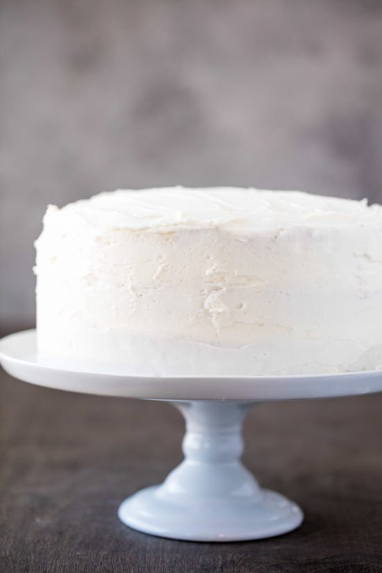 Profile photo of the most amazing white cake with the buttercream frosting on a white cake stand