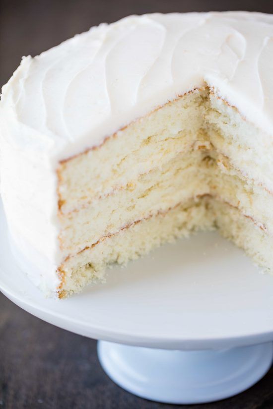 Most Amazing White Cake With Buttercream Frosting On A Cake Stand With Some Slices Taken Out