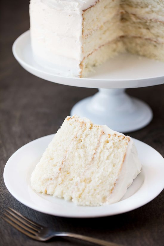 Slice of white cake next to a fork on a white plate with the rest of the white cake in the background on a cake stand on a wood surface