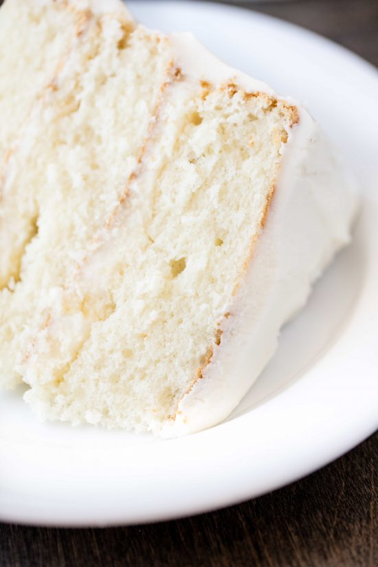 Closeup of a slice of the most amazing white cake on a white plate on a wooden surface