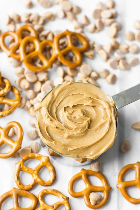 Measuring cup full of peanut butter surrounded by pretzels and peanut butter chips