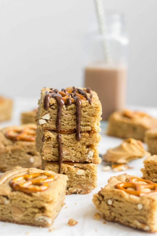 Peanut butter pretzel blondie squares stacked into a pile with chocolate drizzling down the sides