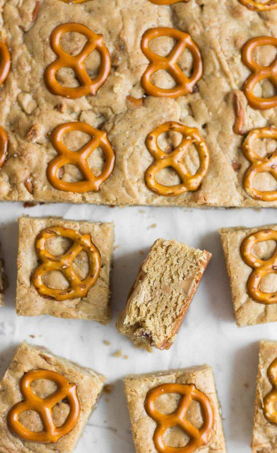 Peanut butter pretzel blondie squares next to a larger sheet of the peanut butter pretzel blondies