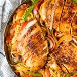 Cajun spiced chicken breasts sliced and served on a bed of linguini with grilled bell peppers, mushrooms and red onion in a skillet