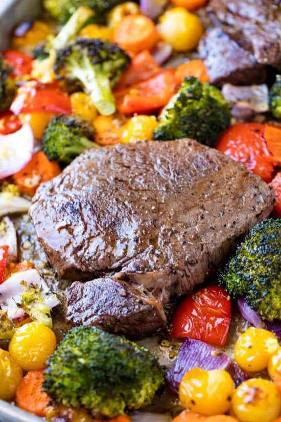 A juicy steak surrounded by roasted broccoli, cherry tomatoes, bell peppers red onion