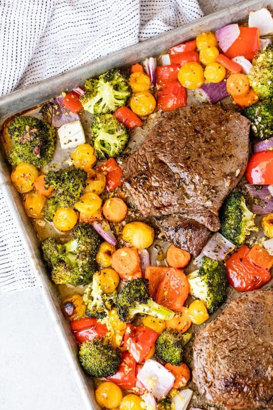 Two steaks are surrounded by roasted broccoli, cherry tomatoes, bell peppers and red onion on a sheet pan
