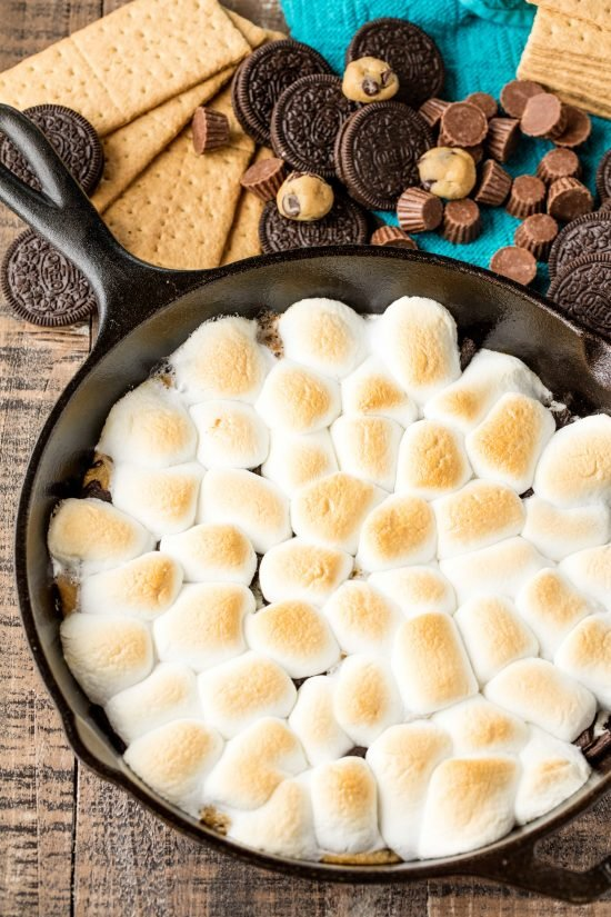 Cast iron skillet full of million dollar skilllet smore's made from marshmallow, cookie dough, oreo, and other melty goodness