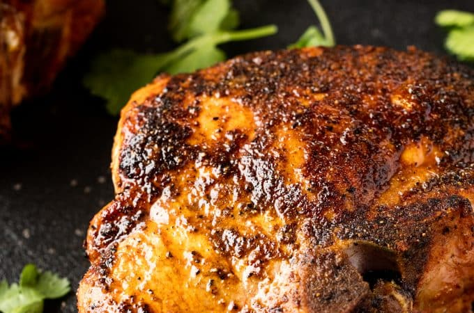 Bone-in smoked pork chops glistening in the light on a black surface with a parsley garnish