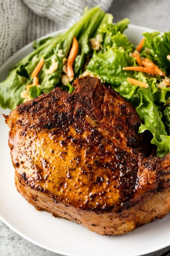 Bone-in smoked pork chop on a plate with some salad greens and carrot pieces
