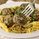 A fork lifts a meatballs from a plate of Swedish meatballs and gravy served over egg noodles on a plate, garnished with fresh parsley.