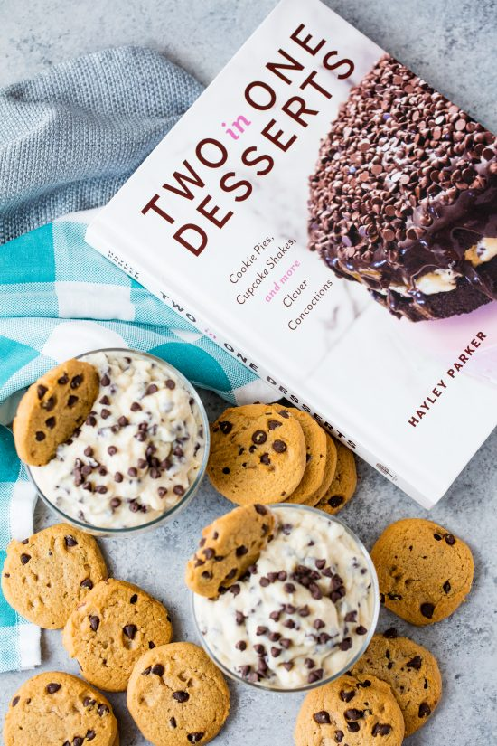"Two cups of chocolate chip cookie dough pudding next to the cookbook ""Two in One Desserts"" by Hayley Parker"
