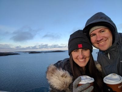 My husband and I with hot chocolate in hand with the ocean and a glimpse of Nynashamn, Sweden in the background