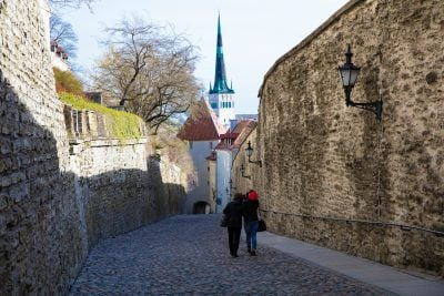 Two people stroll down a cobblestone street surrounded by rock walls and plants dripping over the side. A church steeple in the distance