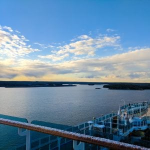 A sweeping view across the cruise ship with ocean, the glimpse of land (Nynashamn) and clouds lit by the sun