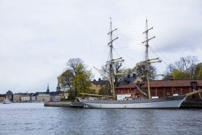A sailboat docked in a bay, the city of Stockholm, Sweden in the background