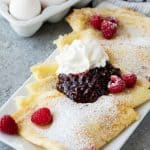 Fluffy Swedish Pancakes served on a platter with fresh raspberries, jam, a dollop of whipped cream and a dusting of powdered sugar