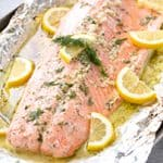 Baked Salmon that has lemon slices, dill, garlic, and butter on it