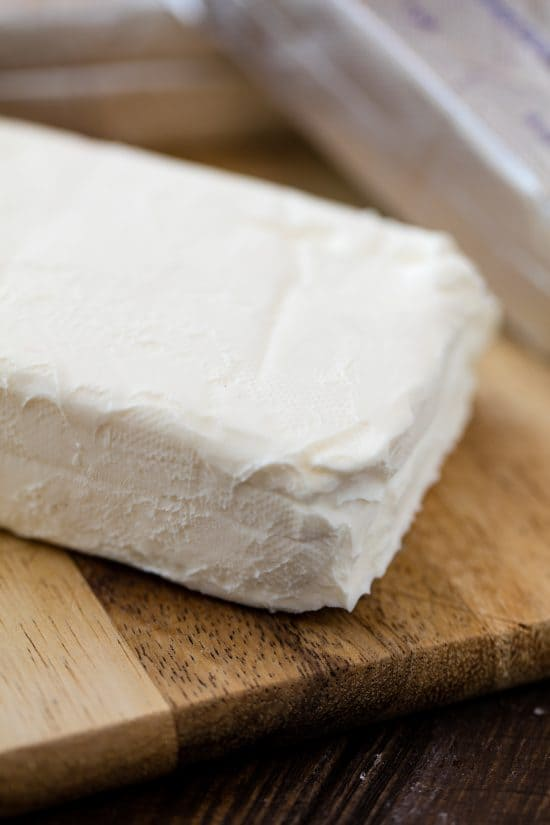 Close up of a block of cream cheese on a cutting board.