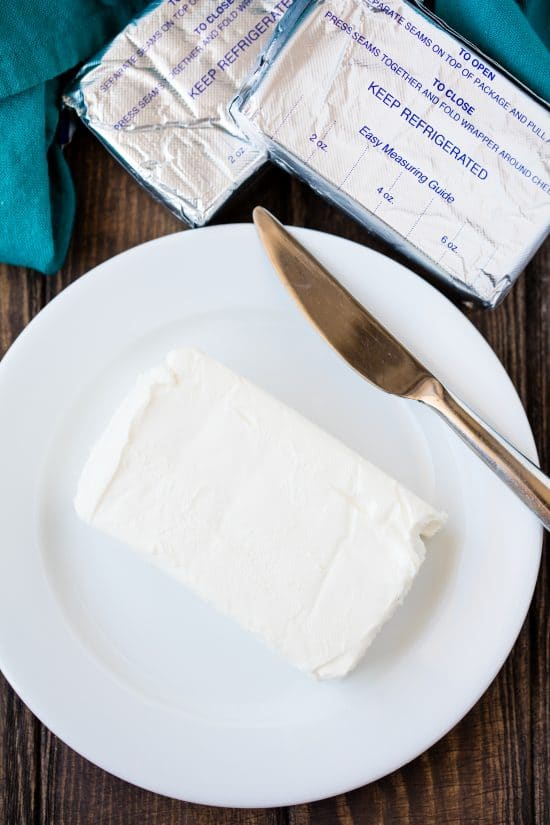 A block of cream cheese on a white plate with a knife on it.