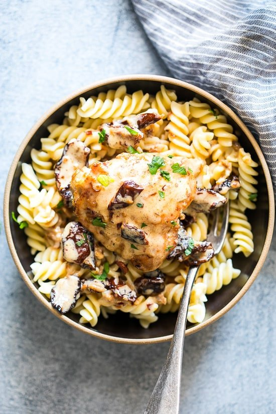 Bird's eye view of a Creamy sun-dried tomato chicken breast on some noodles in a bowl.