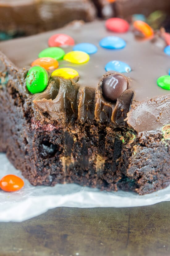 Close up of the side of a M&M Fudge Brownie with a fork bite taken out of it.