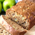 Sliced loaf of moist cinnamon apple bread on a cutting board.