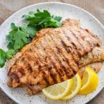 Marinaded cooked chicken on a white plate with lemon slices and cilantro leaves.