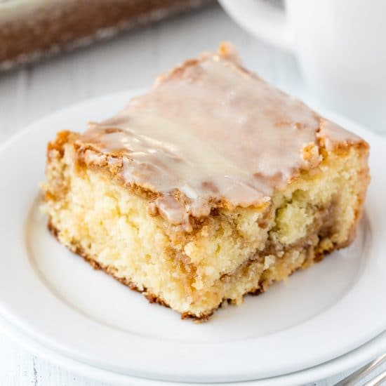 This super moist Cinnamon Roll Swirl Coffee Cake is worth making from scratch! Rich, moist coffee cake is swirled with a cinnamon roll filling and topped off with a simple glaze. This cake is to die for!