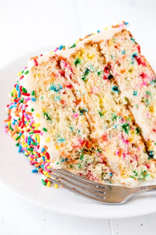 A close up of a slice of Funfetti Birthday Cake with a bite taken out of it on a white plate with a fork on it.