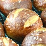 Close up of pretzel rolls cooling on a wire rack.