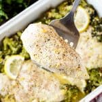 Lemon chicken being held by a spatula over a pan full of lemon garlic chicken broccoli bake.