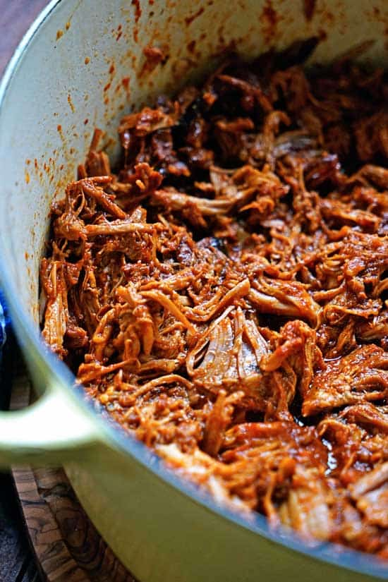 Shredded pork in a ceramic cast iron pot.