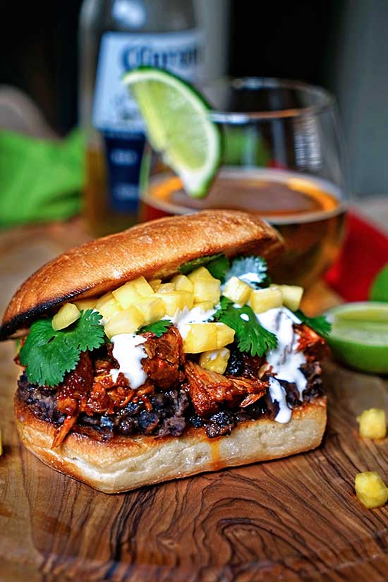 Angeled shot of a Pineapple Chile Pulled Pork Sandwiches sitting on a wood countertop with a drink in the background.
