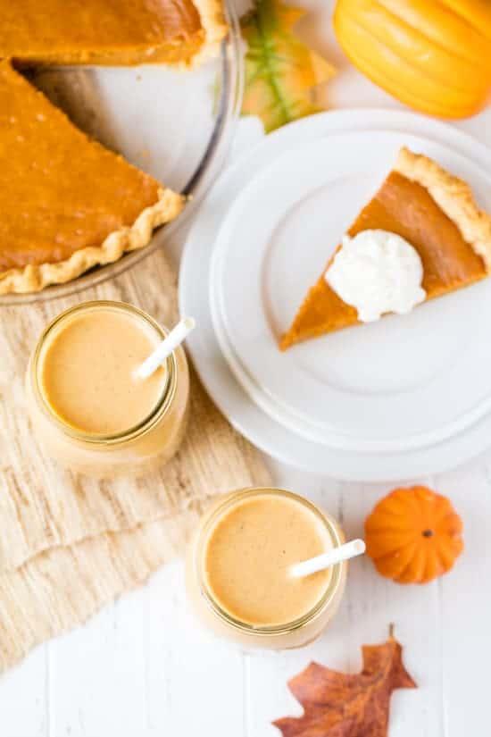 Bird's eye view of pumpkin pie smoothies sitting next to a slice of pumpkin pie and a pumpkin pie.