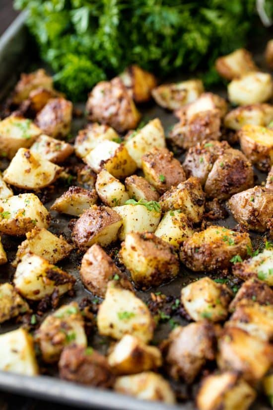 Easy Roasted Parmesan Pesto Potatoes is an easy side dish that is full of flavor. Red potatoes are coated with a basil pesto and parmesan cheese and roasted to perfection. You'll love it!