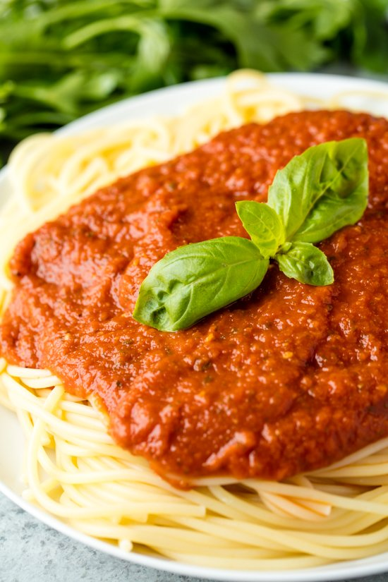 Homemade Spaghetti Sauce served over a plate of spaghetti, garnished with a sprig of fresh basil