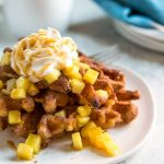 Churro Waffles topped with pineapple, a dollop of whipped cream and drizzled with caramel