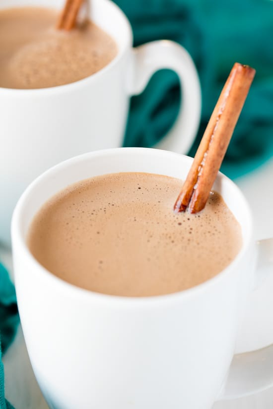 Caramelized Cinnamon Hot Chocolate served in two white ceramic mugs with cinnamon sticks