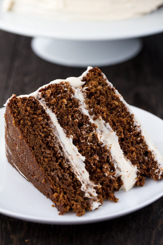 A slice of Christmas Gingerbread Cake with layered with cream cheese frosting on a plate