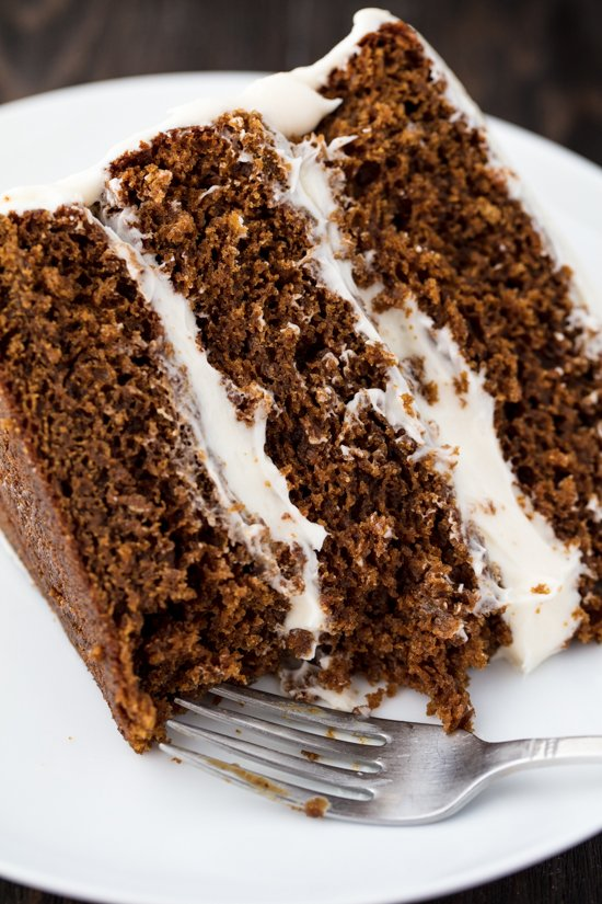 A slice of Christmas Gingerbread Cake with layered with cream cheese frosting on a plate with a bite taken out