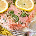 Easy Garlic Herb Baked Salmon topped with freshly chopped parsley and slices of lemon