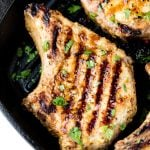 Pan-Grilled Pork Chops in a skillet topped with chopped fresh parsley