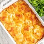 Bird's eye view Cheesy Scalloped Potatoes in a white baking dish.