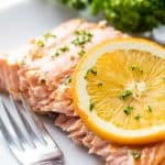 A salmon filet topped with an orange slice and chopped fresh parsley