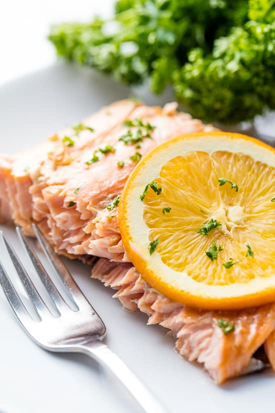 A salmon filet topped with a slice of orange and garnished with chopped fresh parsley