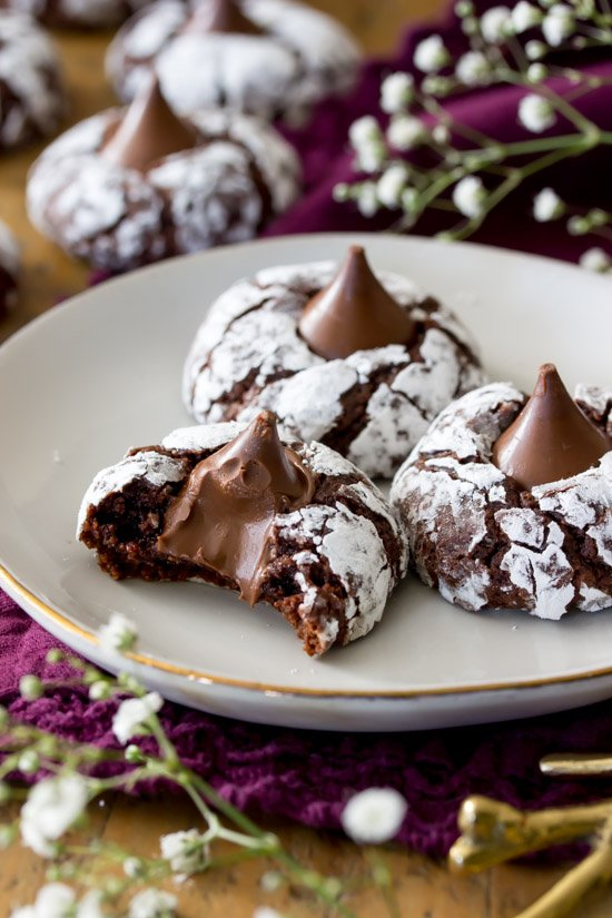 chocolate kiss cookies on a white plate. One has a bite taken out.