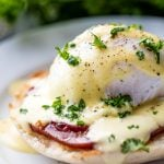 Perfect Eggs Benedict served on a plate, garnished with fresh chopped parsley